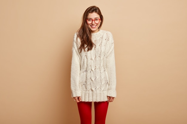 Horizontale aufnahme der positiven europäischen frau in der weißen winterkleidung und in der roten strumpfhose, wirft über beige wand auf, genießt freizeit und ist gut gelaunt. menschen, emotionen, mimik