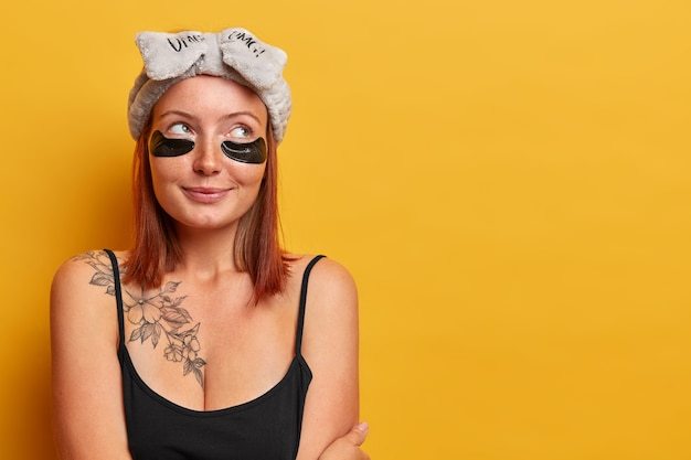 Horizontale aufnahme der reizenden erwachsenen frau gekleidet in ärmellosem schwarzem t-shirt, hat tätowierung auf körper, schaut mit nachdenklichem ausdruck weg, trägt stirnband und hydrogelflecken, kümmert sich um haut und schönheit