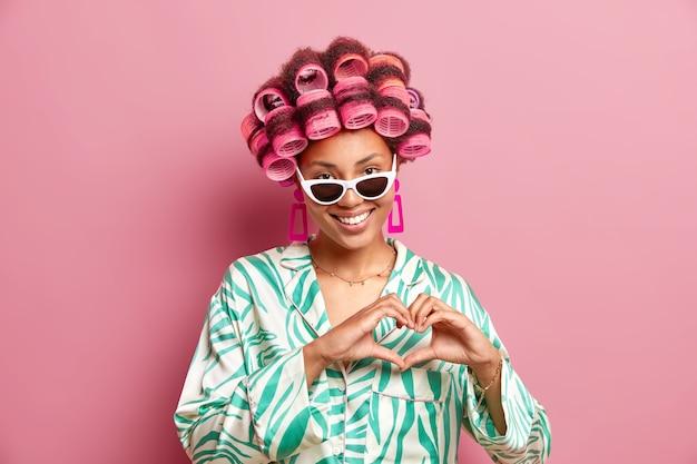 Horizontale aufnahme der ziemlich zufriedenen afroamerikanischen frau wendet haarrollen an, um frisur zu machen, trägt seidenmantel, sonnenbrille und ohrringe, die herzzeichen lokalisiert über rosa wand bilden