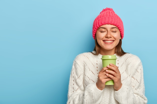 Horizontale aufnahme der zufriedenen europäischen frau entspannt sich mit heißem getränk, hält kaffee zum mitnehmen, lächelt angenehm