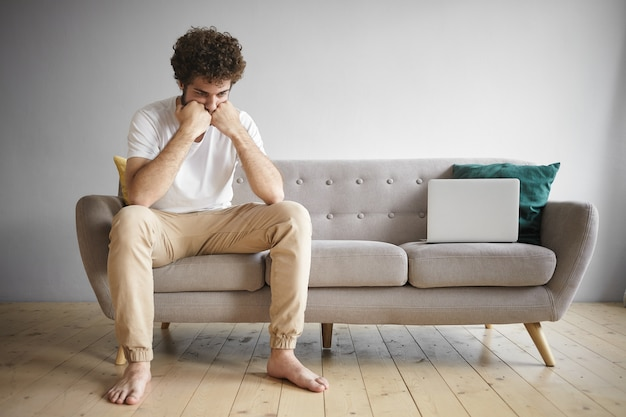 Horizontale aufnahme des arbeitslosen jungen mannes, der weißes t-shirt und beige jeans trägt, die barfuß auf tragbarem computer der sofaarbeit sitzen, traurigen frustrierten gesichtsausdruck, der online nach arbeit sucht