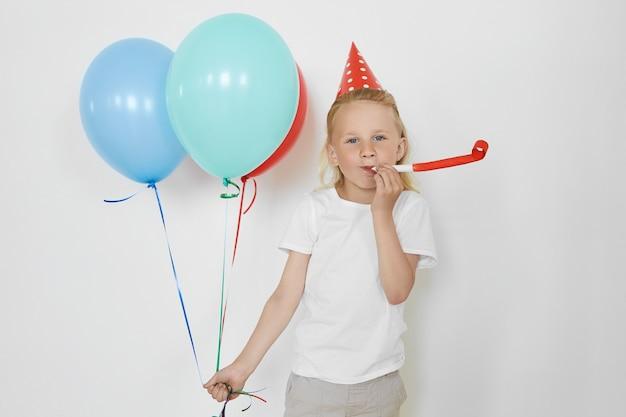 Horizontale aufnahme des blonden hübschen europäischen geburtstagskindes, der freizeitkleidung und roten kegelhut trägt, party genießt, horn bläst, bunte luftballons hält, mit glücklichem ausdruck