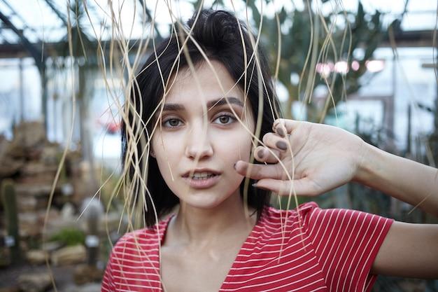 Horizontale aufnahme des charmanten bobhaarigen jungen weiblichen einkaufens im gartencenter, das gegen unscharfen hintergrund von pflanzen mit strohhalmen steht, die vor ihr herabhängen. gartenarbeit und landwirtschaft