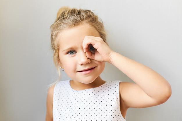 Horizontale aufnahme des entzückenden hübschen mädchens im schönen kleid, das durch das fernglas schaut, das von ihrer hand gemacht wird und daumen mit vorderfinger verbindet. nettes lustiges weibliches kind, das spaß hat, spionage