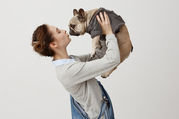 Horizontale aufnahme des erwachsenen mädchens in jeansoveralls, die niedlichen welpen küssen, während sie ihn in der luft erhöhen. junges mädchen, das in ihren hund verliebt ist, der im trendigen pullover gekleidet ist. anzeige der zuneigung