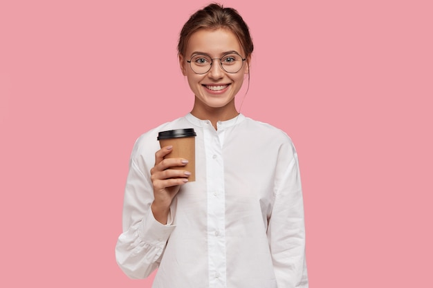 Horizontale aufnahme des glücklichen kaukasischen mädchens im weißen hemd, trägt pappbecher mit kaffee, schlagen sie vor, zu trinken