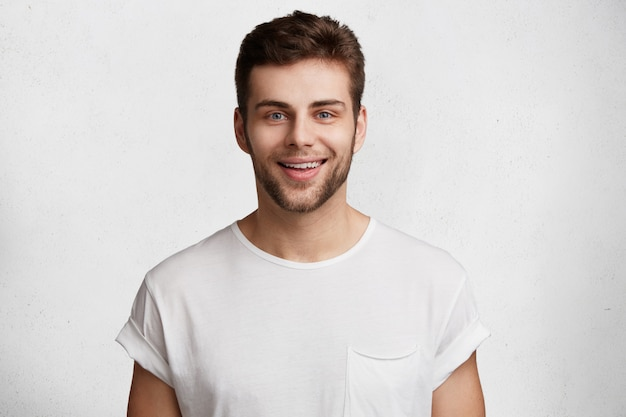 Horizontale aufnahme des hübschen jungen mannes mit blauen augen und borsten, hat positiven ausdruck