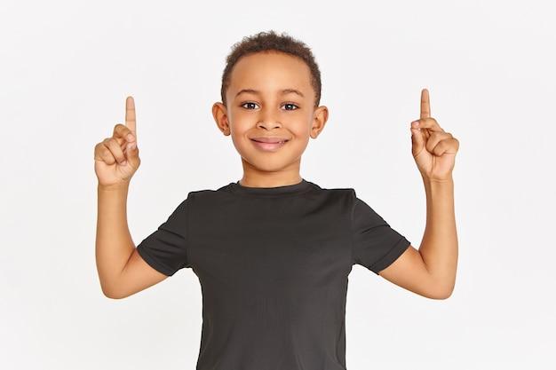 Horizontale aufnahme des hübschen sportlichen afroamerikanischen jungen im stilvollen schwarzen t-shirt, das lokal mit den angehobenen vorderfingern aufwirft, die zeigefinger nach oben zeigen und kopienraum für ihre informationen zeigen