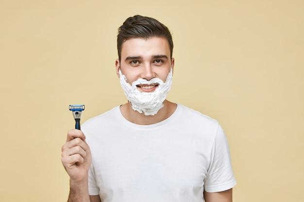 Horizontale aufnahme des lustigen gutaussehenden jungen mannes mit weißem schaum auf seinem gesicht mit lächeln, rasierstab haltend, ti rasieren bart, morgenroutine machend. pflege und männerschönheit