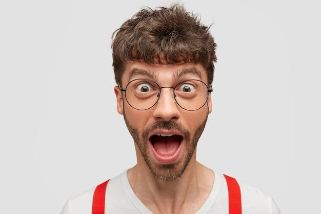 Horizontale aufnahme des lustigen jungen mannes öffnet mund mit überraschung, geknallte augen