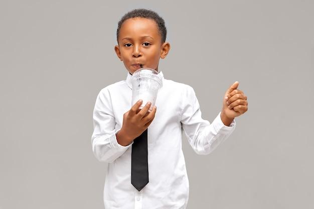 Horizontale aufnahme des niedlichen dunkelhäutigen jungen, der weißes hemd und schwarze krawatte trägt, die frischen saft genießen. hübscher afroamerikanischer schüler, der smoothie oder milchshake aus plastikglas unter verwendung von stroh trinkt