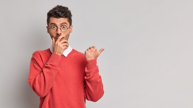 Horizontale aufnahme des schockierten mannes bedeckt mund starrt in die kamera mit abgehörten augen zeigt daumen weg auf leeren raum