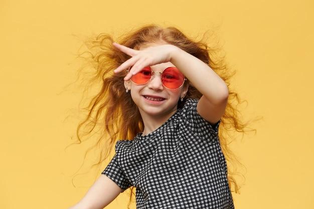 Horizontale aufnahme des schönen glücklichen trendigen kleinen mädchens mit dem lockigen ingwerhaar, das tanzend genießt, mit fröhlichem breitem lächeln, sonnenbrille tragend. musik, tanz, spaß und kinderkonzept