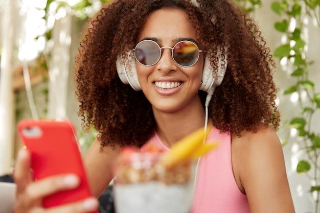 Horizontale aufnahme des schönen jungen weiblichen modells mit dunkler haut und lockigem haar, trägt sonnenstrahlen, verbunden mit kopfhörern und smartphone, hört audiospur. menschen- und unterhaltungskonzept