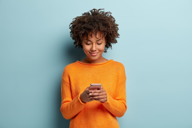 Horizontale aufnahme des schönen zufriedenen weiblichen teenagers fokussiert in smartphone-gerät, chats online mit freunden