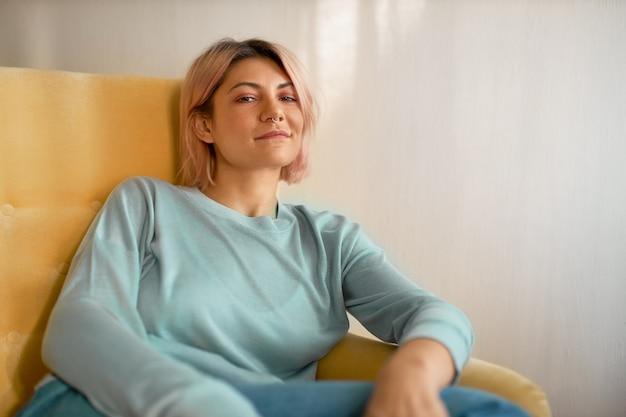 Horizontale aufnahme des stilvollen hübschen mädchens mit bob-rosa-frisur und nasenring, die bequem im sessel sitzen und kamera mit sorglosem entspanntem lächeln betrachten.
