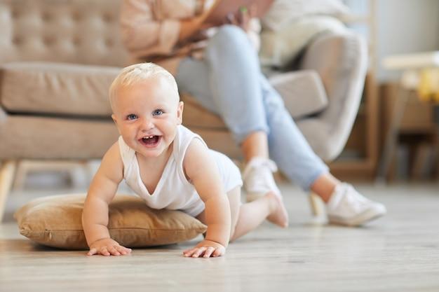 Horizontale aufnahme des verspielten babys, das spaß auf boden im wohnzimmer hat, während seine mutter auf sofa sitzt und buch liest