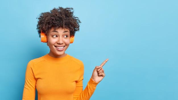 Horizontale aufnahme einer angenehm aussehenden afro-amerikanerin hört einen audiotrack, der in lässigen orangefarbenen jumper-punkten auf blauem kopierraum gekleidet ist, schlägt vor, promo zu sehen, die ankündigung zeigt