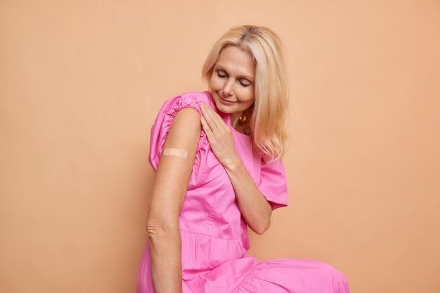 Horizontale aufnahme einer blonden frau, die aufmerksam auf den arm mit geimpftem gips schaut, baut immunität gegen coronavirus auf, trägt rosa kleid isoliert über beige wand