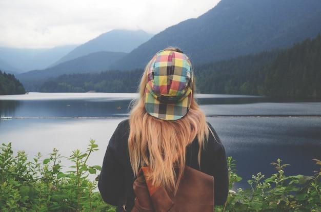 Horizontale aufnahme einer blonden frau mit einer bunten kappe, die den wasserkörper betrachtet