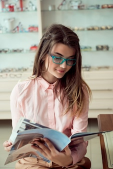 Horizontale aufnahme einer gut aussehenden kaukasischen kundin, die in einer trendigen vorgeschriebenen brille sitzt, eine zeitschrift liest und lächelt und in der warteschlange auf einen augenarzt für eine regelmäßige sichtprüfung wartet