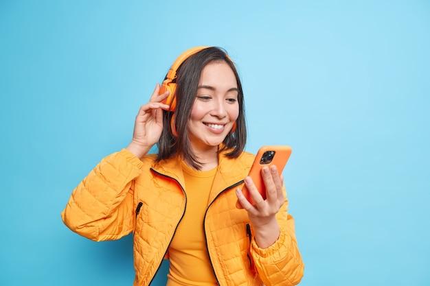 Horizontale aufnahme einer hübschen asiatischen frau erhält eine nachricht in sozialen netzwerken, die sich auf das smartphone konzentriert, hört musik über drahtlose kopfhörer, während sie eine orangefarbene jacke trägt, die über blauer wand isoliert ist