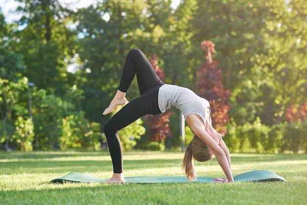 Horizontale aufnahme einer jungen flexiblen frau, die im freien am park ausübt, die ihren rücken gesund sportlichen lebensstil gymnastikakrobatikkonzept streckt.