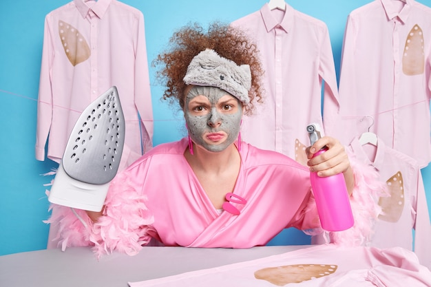 Horizontale aufnahme einer lockigen jungen frau, die wütend aussieht, hält flaschenspray mit wasser und bügeleisen trägt eine hausrobe-schlafmaske auf der stirn posiert gegen gebügelte kleidung herum