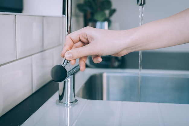 Horizontale aufnahme einer menschlichen hand, die das moderne waschbecken für den wasserfluss öffnet
