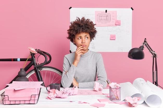 Horizontale aufnahme einer nachdenklichen afroamerikanischen frau, die im coworking space posiert, hat einen nachdenklichen ausdruck und macht ein architekturprojekt, das skizzen für die gestaltung eines neuen gebäudes zeichnet, planungen oder annahmen macht