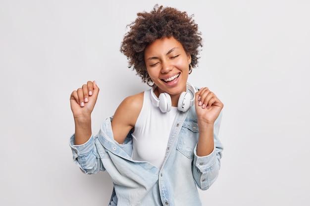 Horizontale aufnahme einer unbeschwerten frau, die im rhythmus von musoc tanzt, schließt die augen vor lustbewegungen und fängt aktiv jedes lied ein, das in jeansjacken-kopfhörern um den hals gekleidet ist