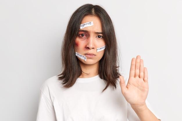 Horizontale aufnahme einer ypung-asiatin macht eine stopp-geste und bittet darum, sie nicht mehr zu verletzen, wird opfer sexueller übergriffe und hat geprellte haut in einem lässigen t-shirt