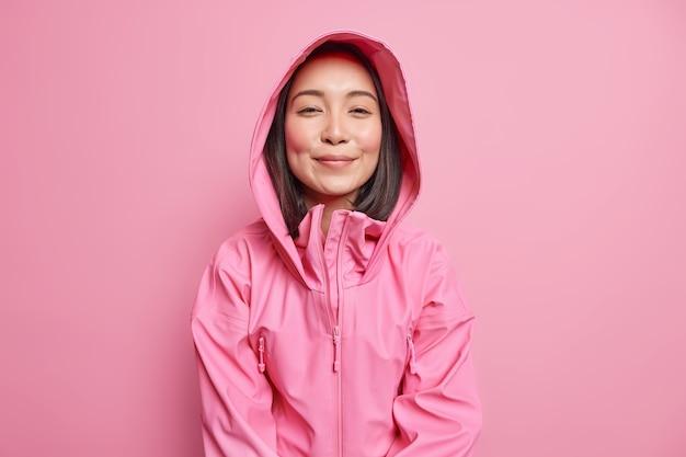Horizontale aufnahme einer zufriedenen, entschlossenen asiatin hat dunkles haar sieht zufrieden aus, trägt eine rosa jacke mit kapuzenkleidern für regenwetterposen im innenbereich. menschen kleiden emotionen konzept.