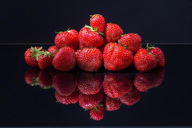 Horizontale aufnahme eines haufens roter kroatischer erdbeeren auf einer schwarzen reflektierenden oberfläche