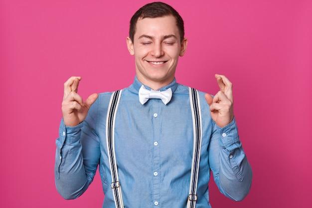 Horizontale aufnahme eines hoffnungsvollen jungen mannes, der mit gekreuzten fingern posiert, die augen geschlossen hält, ein blaues hemd mit hosenträgern und einer weißen fliege anzieht, möchte, dass seine träume wahr werden, und über die prüfungsergebnisse nachdenkt.