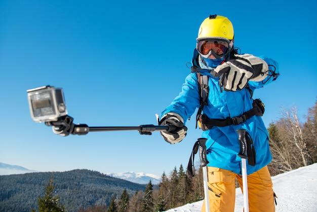 Horizontale aufnahme eines männlichen skifahrers, der spaß im freien macht, der ein selfie mit aktionskamera auf einem einbeinstativ nimmt