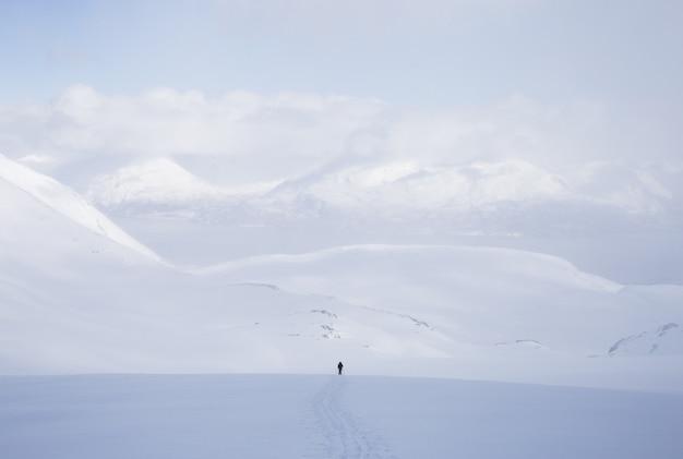Horizontale aufnahme eines mannes, der in einem schneebedeckten gebiet mit vielen hohen bergen steht, die mit schnee bedeckt sind