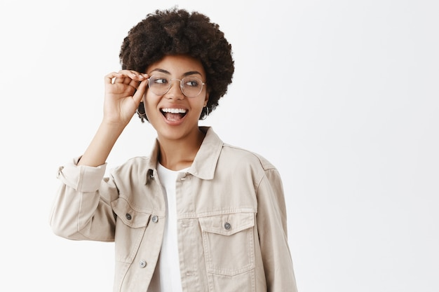 Horizontale aufnahme eines sorglosen, selbstbewussten lesbischen afroamerikaners in einer brille und einem beigen hemd, die den rand einer brille berühren und nach rechts blicken und weitgehend selbstbewusst und glücklich lächeln