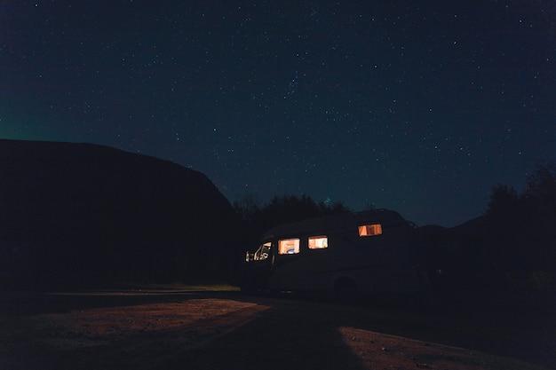 Horizontale aufnahme eines weißen fahrzeugs mit lichtern unter dem schönen sternenhimmel bei nacht