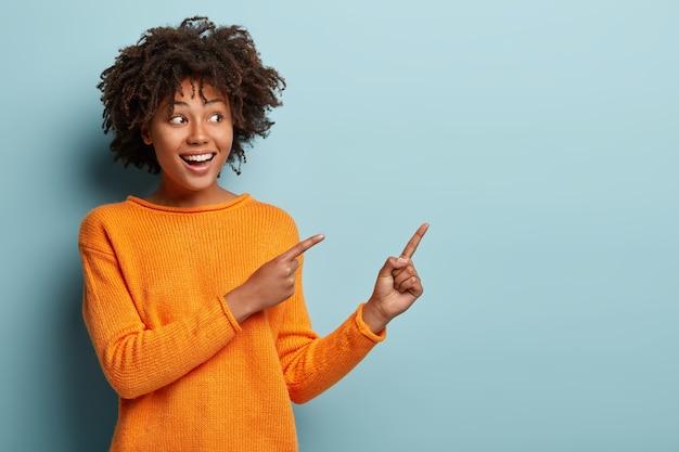 Horizontale aufnahme erfreut dunkelhäutige frau mit afro-haarschnitt, zeigt mit beiden vorderfingern weg, zeigt leerzeichen für ihre beförderung, isoliert über blaue wand. menschen, werbekonzept