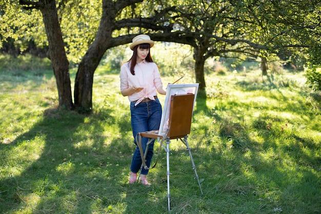 Horizontale aufnahme in voller länge einer hübschen jungen kaukasischen frau, die strohhut, jeans und rosa hemd trägt und draußen im park auf leinwand malt.