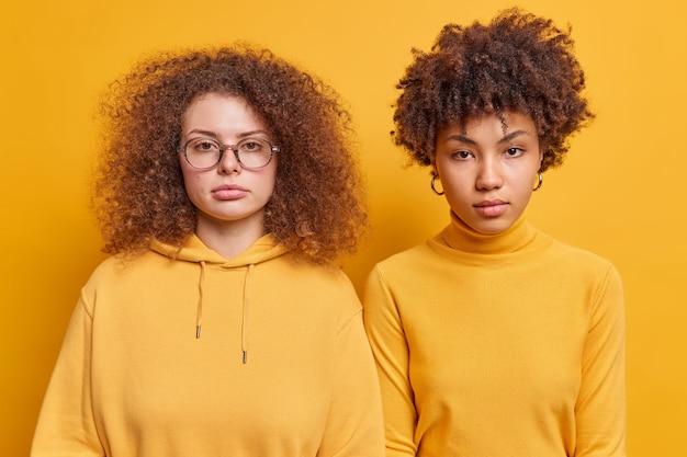 Horizontale aufnahme verschiedener weiblicher begleiter, die nebeneinander stehen, sehen ernsthaft aus, haben aufmerksamen blick, der beiläufig gekleidet ist und informationen isoliert über gelber wand hört
