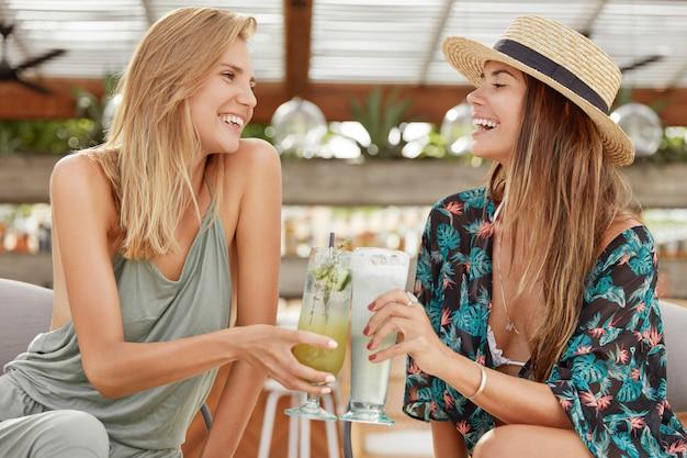 Horizontale aufnahme von entzückenden frauen, die gut gelaunt sind, zusammen mit cocktails ruhen, gläser klirren, spaß haben. freundinnen reisen in ein exotisches land, trinken tropische getränke. freundschaftskonzept