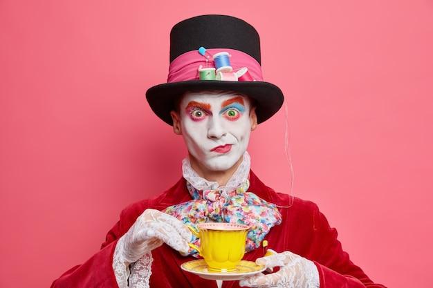 Horizontale aufnahme von ernsthaften männlichen hutmacher-posen mit tasse tee trägt hut hat manieren von aristokratischen gentleman-kleidern für maskerade-karneval-posen im innenbereich