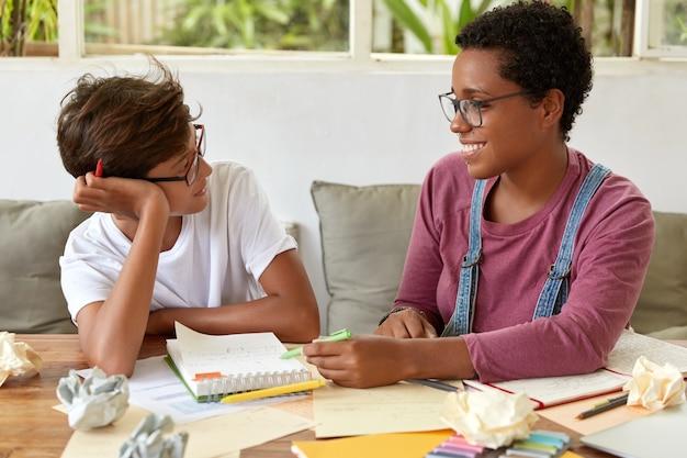 Horizontale aufnahme von frauen gemischter rassen haben konversation während des lernprozesses
