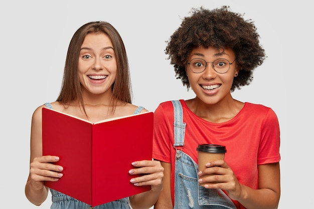 Horizontale aufnahme von fröhlichen zwei interracial studenten lesen buch, lernen material für bevorstehende prüfung, trinken heißen kaffee zum mitnehmen