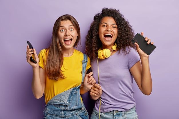 Horizontale aufnahme von glücklichen besten freunden treffen sich am wochenende, haben spaß mit modernen technologien, tanzen zu musik, schauen gerne in die kamera