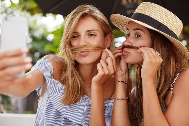 Horizontale aufnahme von glücklichen frauen machen selfie, haben spaß zusammen, in hochstimmung, dumm zusammen im freien, haben ruhe während der sommerferien. homosexuelle paare machen fotos für soziale netzwerke
