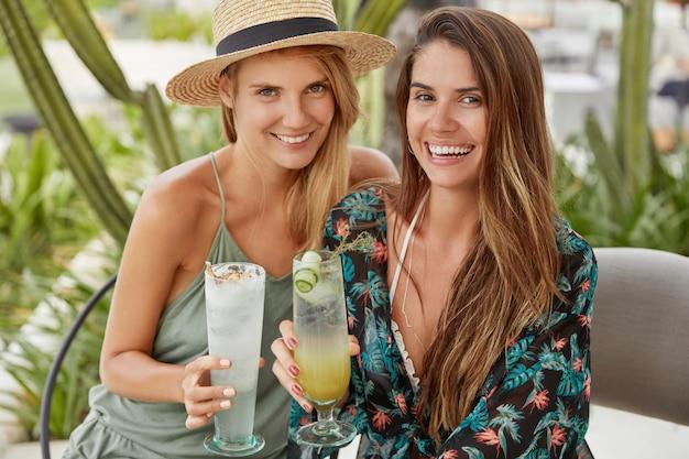 Horizontale aufnahme von glücklichen jungen frauen genießen gute sommerruhe, klirren gläser mit cocktails, sitzen zusammen im terrassencafé. homosexuelles paar kommt auf party, freut sich zu kommunizieren, hat freizeit