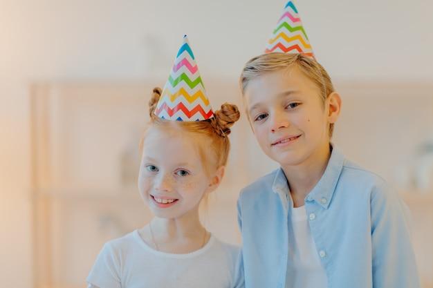 Horizontale aufnahme von glücklichen mädchen und jungen trägt kegelpartyhüte, feiern geburtstag zusammen